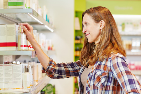 Elderly attractive woman buying cosmetics in a drugstore photo