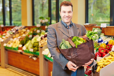 Happy elderly man shopping for fresh vegetables in a supermarket photo