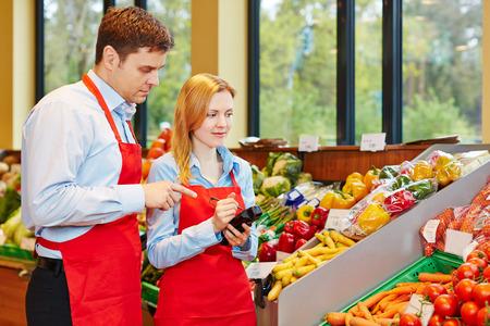 tiendas de comida: Mujer joven que hace el aprendizaje en el supermercado recibe ayuda de gerente de la tienda Foto de archivo