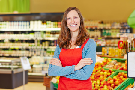 Portrait of smiling female store manager in a supermarket with her arms crossed photo