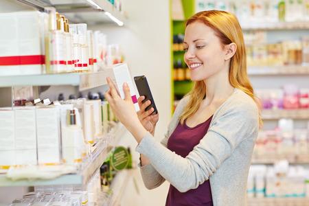 codigos de barra: Mujer de Youn comparando con su smartphone de los precios en el departamento de farmacia de un supermercado Foto de archivo