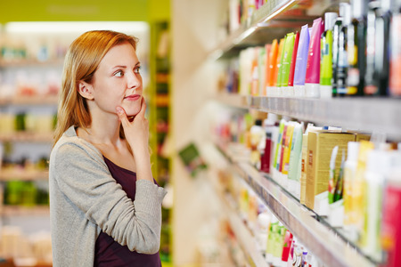 skin care products: Young woman shopping selective and sustainable in a supermarket