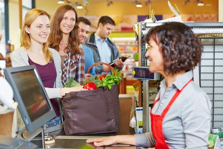 Mujer con alimentos haciendo cola en la caja del supermercado