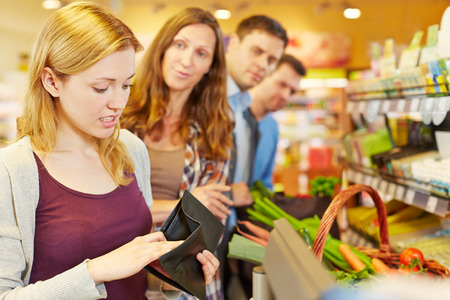 to queue: Embarrassed woman looking for money in her wallet at supermarket checkout Stock Photo