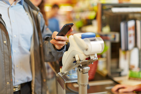 Man paying wireless with his smartphone at supermarket checkout photo