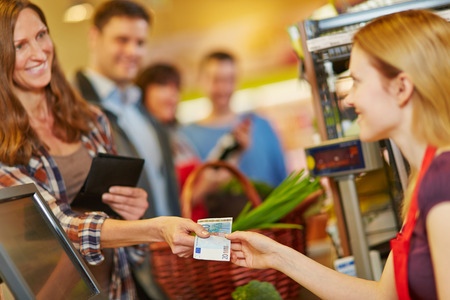 tiendas de comida: Mujer sonriente que paga con el dinero de ley de euros en la caja del supermercado