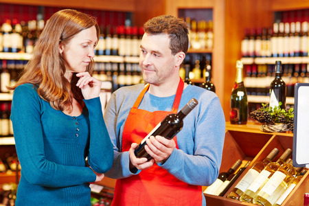 Salesman giving elderly woman advice on buying bottle of red wine