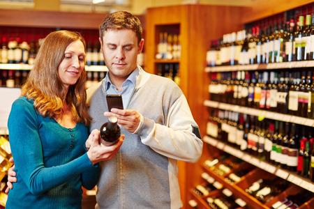 Mann unter Bild der Weinflasche im Supermarkt mit seinem Smartphone Standard-Bild