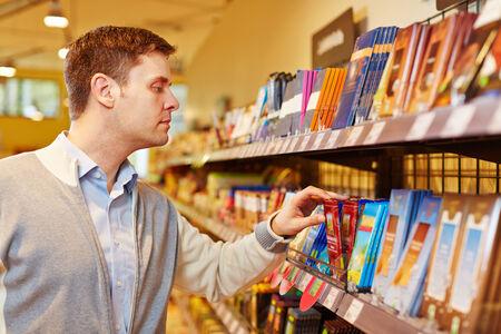 Hombre que compra barra de chocolate en un supermercado Foto de archivo