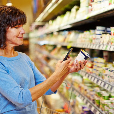 Elderly woman with smartphone scanning barcode of yogurt in a supermarket Stock Photo