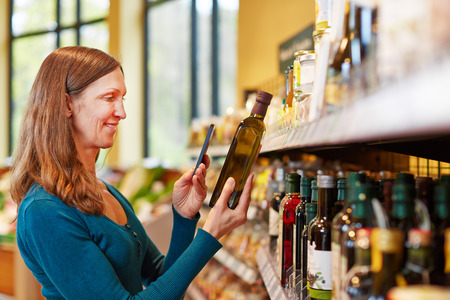 Smiling woman scanning a bottle of olive oil in a supermarket with her smartphone photo