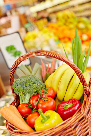 Different fresh vegetables and fruits in shopping basket in a supermarket