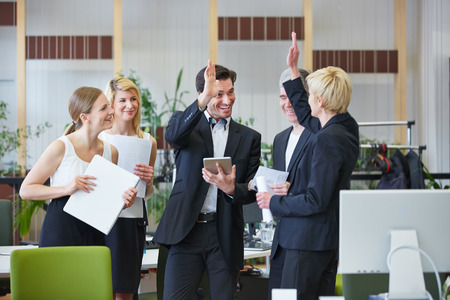 Happy business team giving high five with hands in the office