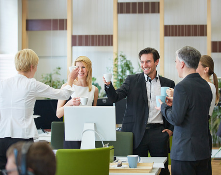 Groep bedrijfsmensen die koffie drinken in het kantoor tijdens de pauze