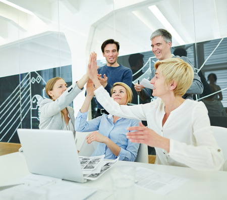Successful business team with laptop computer giving High Five
