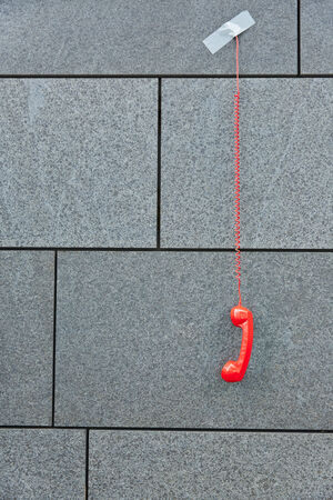 cry for help: Red phone hanging down taped to a grey wall