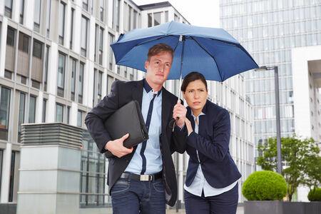 sotto la pioggia: Due uomini d'affari a piedi sotto la pioggia sotto un ombrello in citt�