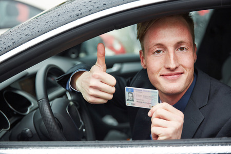 Young proud man in a car holding drivers licence and his thumps up