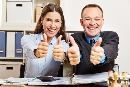 Successful office business team holding their thumbs up and smiling