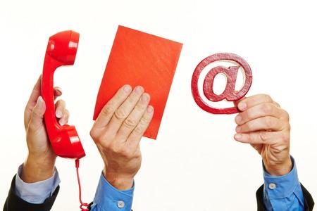 comunicar: Muchas manos con teléfono y correo como concepto de comunicación