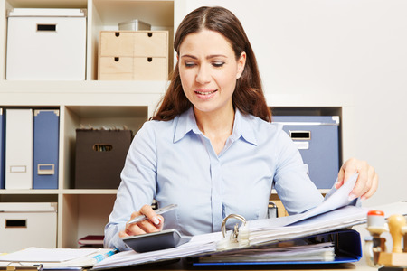Finance clerk in office calculating financing with calculator and files