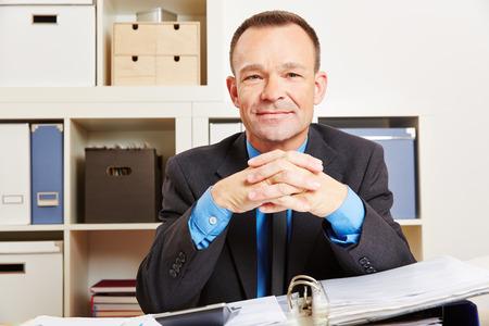 administracion de empresas: Contador sentado en su escritorio en la oficina con los archivos y una calculadora