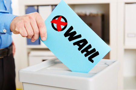 plebiscite: Hand with ballot paper on ballot box during election