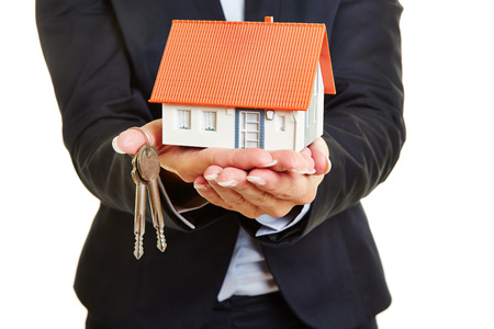 occupancy: Hands of a female real estate broker holding a small house and keys