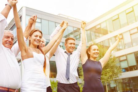 Vele gelukkige mensen houden hun armen omhoog en juichen