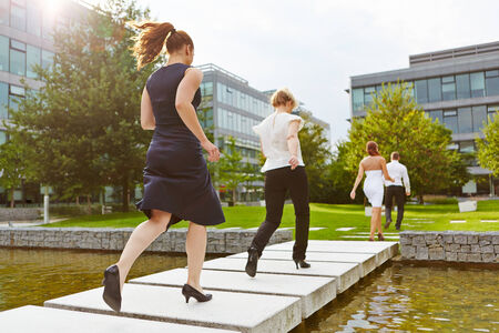Many business people running over a bridge in front of the office photo