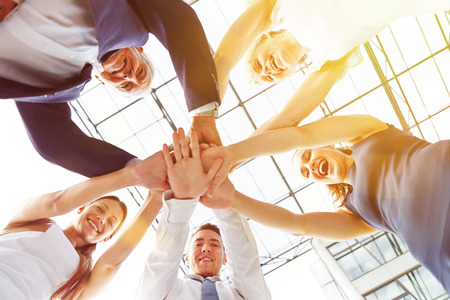 economy: Happy group of businesspeople stacking their hands in cooperation