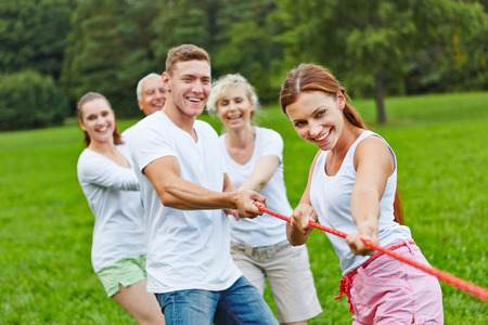 Strong group in a competition playing tug of war Stockfoto
