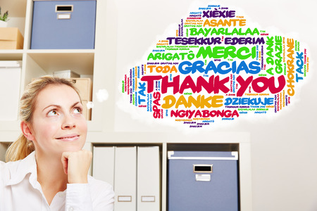 employee satisfaction: Woman in office thinking about thank you in many different languages