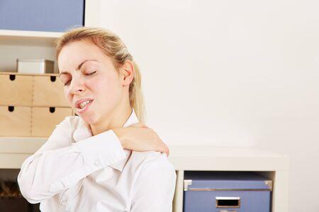 convulsion: Mujer de negocios de pie en la oficina con dolor en su hombro Foto de archivo