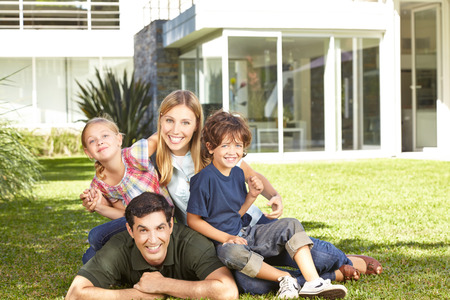 people laughing: Happy family with two children laying in a garden in front of modern house Stock Photo