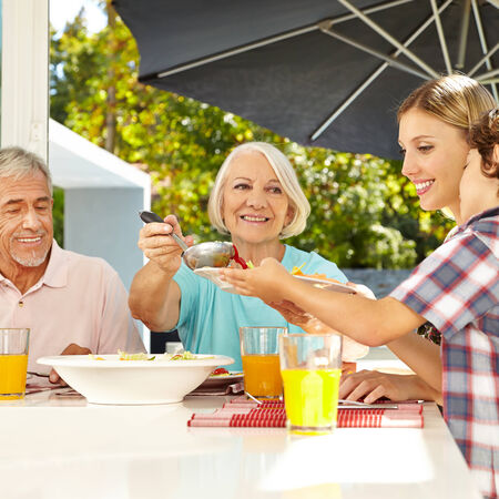 sunroom: Grandmother serving lunch to grandson at table with a ladle Stock Photo