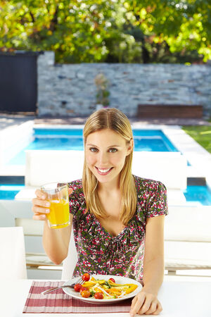 sunroom: Smiling vegetarian woman eating salad with juice at lunch