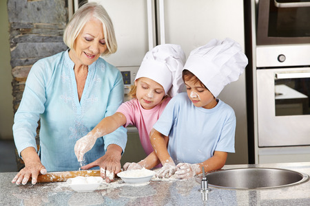 Family with grandmother and children baking christmas cookies in kitchen
