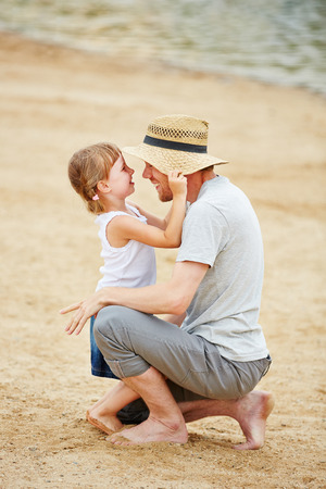 single father: Single father playing with his daughter on beach in summer