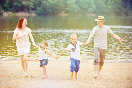 jezior: Szczęśliwa rodzina z dziećmi o wakacjach na jeziorem z plaży