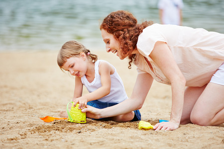 sandpit: Family with mother and daughter playing in sand of beach Stock Photo