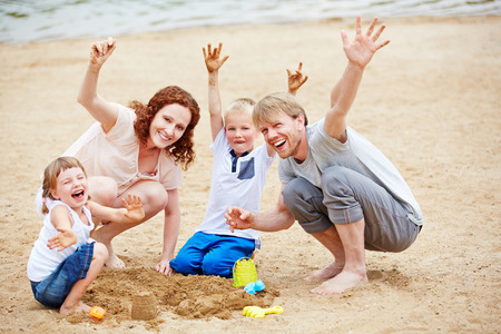 Family with two children cheering in summer on beach while building a sand castle