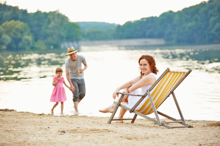 lake beach: Family with daughter taking summer vacation at beach of a lake