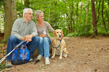 taking a break: Happy senior couple with dog taking a break in a forest Stock Photo