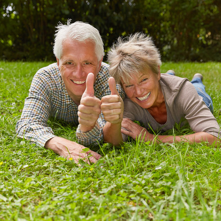 Happy senior couple holding two thumbs up for congratulation