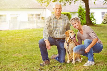 Happy senior couple sitting with house and labrador retriever in a garden photo