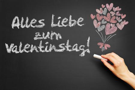 Liebe: Hand writes in German Alles Liebe zum Valentinstag! (Happy Valentins Day!) on blackboard