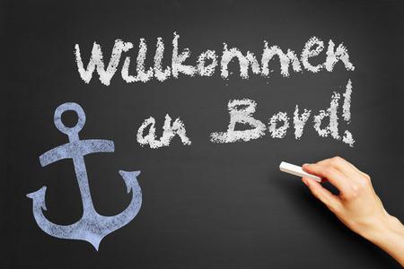 willkommen: Hand writes in German Willkommen an Bord! (Welcome aboard!) on blackboard