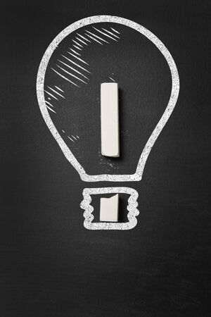 Lightbulb and exclamation point illustrating concept of idea on blackboard photo