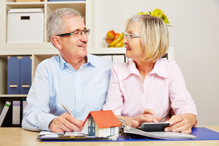 planificacion familiar: Feliz altos pareja planificaci�n financiamiento hipotecario en conjunto para construir una casa Foto de archivo